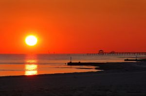 The sun sets over the water in Pass Christian, Mississippi Dec. 8, 2010. The Gulf Coast continues to recover from this summer's Deepwater Horizon BP oil spill, which affected nearly 29,000 square miles of shoreline from Louisiana to Florida. (Photo by Carmen K. Sisson/Cloudybright)